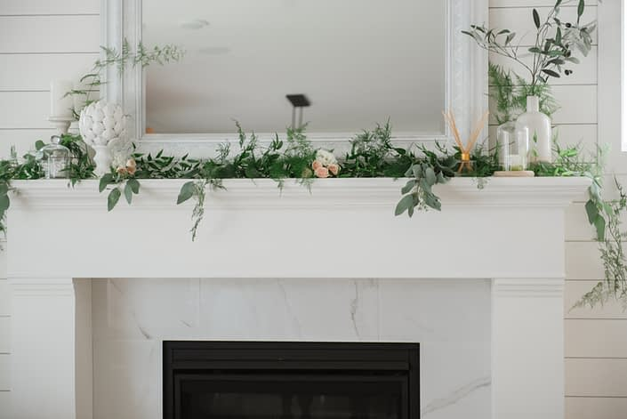 White mantle fireplace with eucalyptus, plumosa and italian ruscus greenery and accents of pale peach spray roses