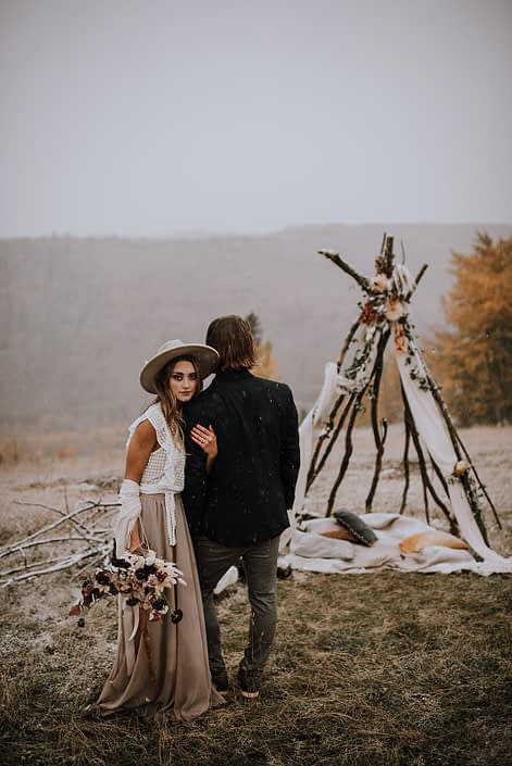 couple standing next to a tee pee for down the aisle fall styled shoot with fall coloured flowers