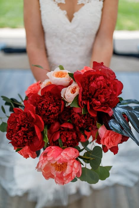 bridal bouquet designed with burgundy and coral peony, black monstera, eucalyptus and peach garden roses