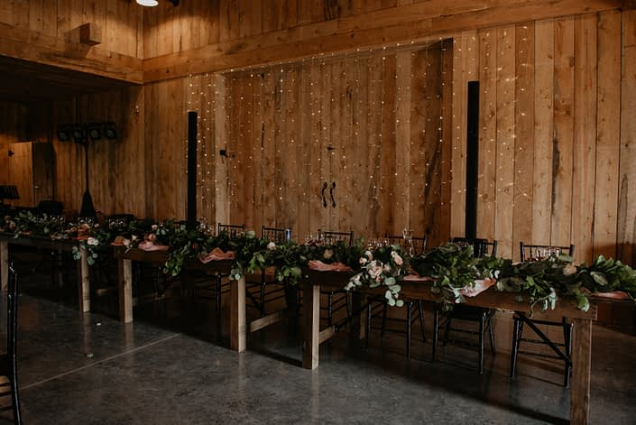 Head table covered in a fresh greenery garland with barn wall backdrop and twinkly lights.