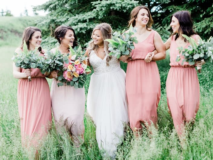 Bride, Taylor and her bridesmaids - Taylor is carrying a modern coral charm peony bouquet with accents of golden mustard roses, quicksand roses, cappuccino roses, astilbe, boston fern, monstera leaf and eucalyptus greenery. Bridesmaids are carrying bouquets made a mixed variety of eucalyptus and boston fern greenery.