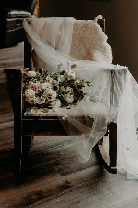 Erika's blush, ivory and white bridal bouquet on a wooden rocking chair with her veil.