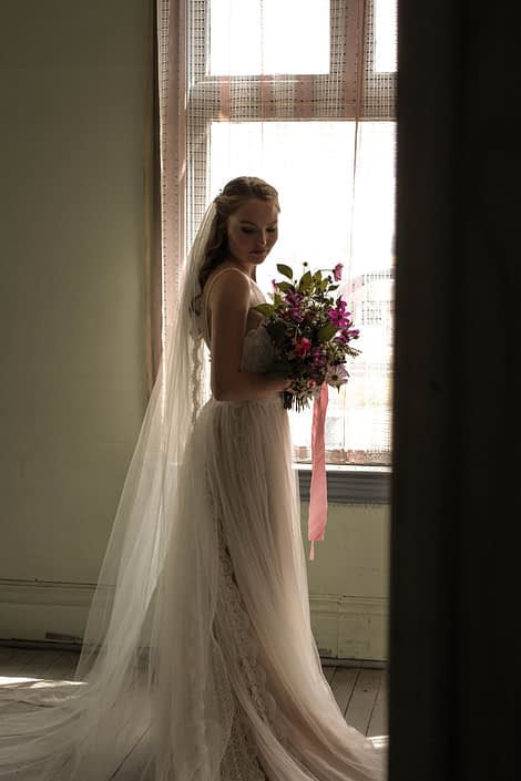 Pink Vintage Photoshoot - model wearing ivory bridal gown and veil holding white, pink and purple wildflower bouquet made of cosmos and greenery tied with trailing ribbons.