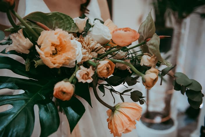 Bridal bouquet make with tropical anthurium, monstera leaves, peach poppies and ranunculus and cinerea eucalyptus