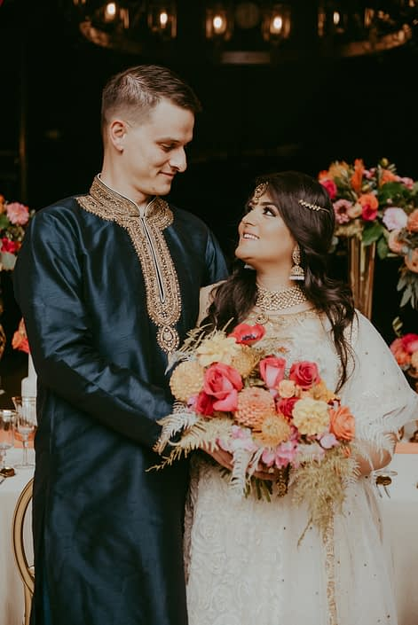 Bride and groom with ombre fuchsia and orange bridal bouquet designed with roses, dahlias, anemones, bleached bracken fern and gold plumosa