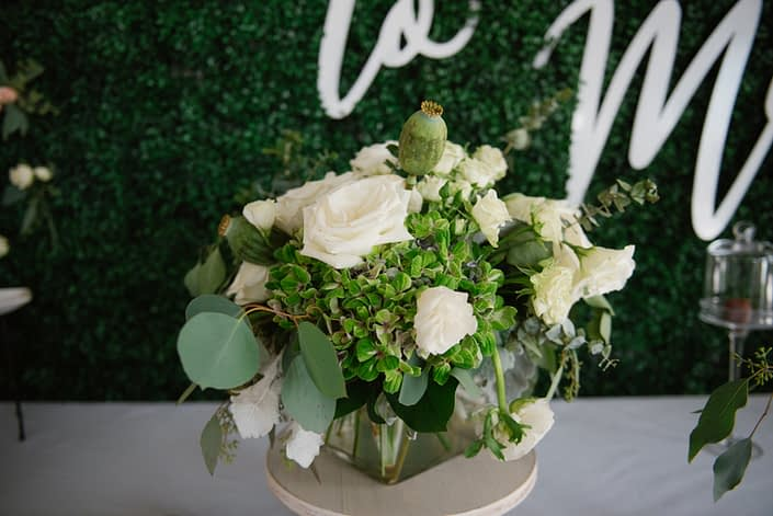 Floral arrangement with boxwood backdrop designed in a clear glass vase with green hydrangea, white roses and white ranunculus