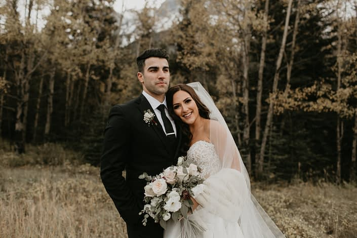 Brittany and Briggs with ivory and blush bridal bouquet featuring burgundy astrantia, white o'hara garden roses, lisianthus, ranunculus, quicksand roses and eucalyptus greenery