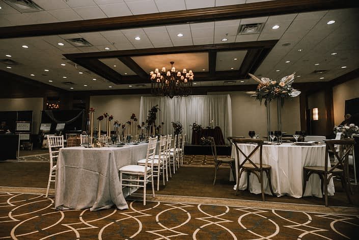 Cambridge Bridal Show 2020 - long table with white chairs decorated with tall gold centrepieces made of red roses and round tables with wood chairs and tall structural arrangement with metallic dyed Anahaw palm leaves, pampas grass, blush roses and greenery.
