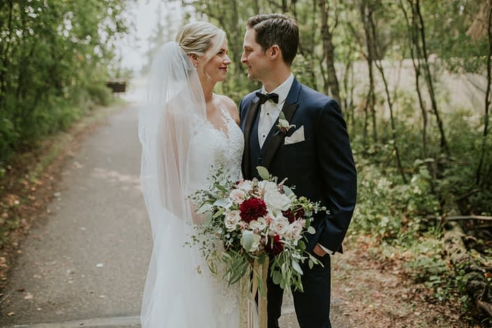 Bride with cathedral length veil and lace wedding dress with groom in navy tux with spray rose boutonniere holding a burgundy, blush and ivory bridal bouquet with eucalyptus collar