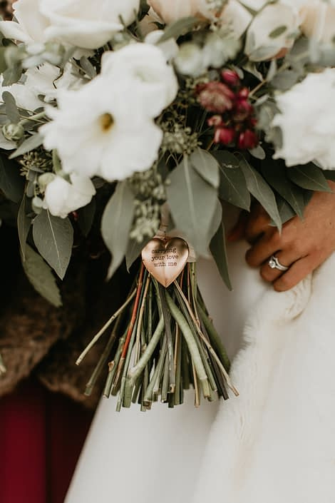 Rose gold heart shaped locket wrapped around the bridal bouquet handle.