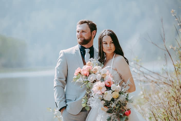 Bride and groom with a crescent shaped bouquet designed with coral charm peonies, quicksand and playa blanca roses, peach ranunculus, pale pink astilbe, metallic silver plumosa and eucalyptus greenery.