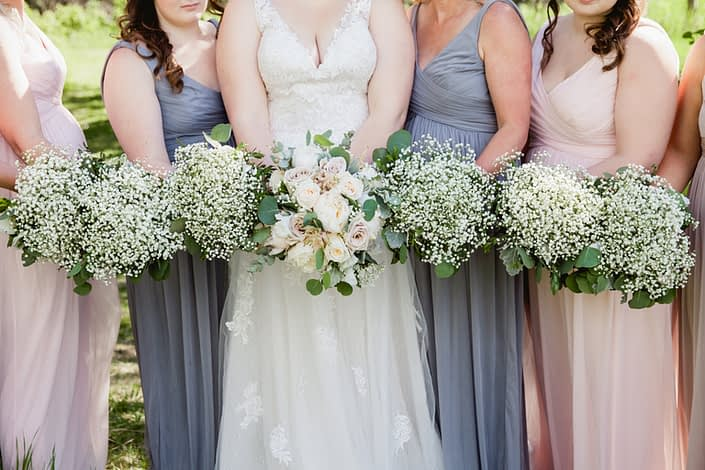 Close up of Kuera and her bridesmaid's vintage chic bouquets; Kuera is wearing a lacey white gown and holding a cream and blush bouquet featuring white peonies, white o'hara garden roses, quicksand roses, pale pink astilbe, babies breath, dusty miller and eucalyptus; bridesmaids are wearing dusty blue, blush or grey dresses and holding babies breath bouquets with eucalyptus and dusty miller collars.