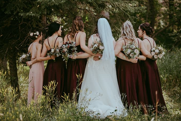Bride with bridal party; bridesmaids wearing burgundy with blush bouquets; flower girl wearing dusty rose with burgundy and dusty rose bouquet; bride with burgundy and dusty rose bouquet