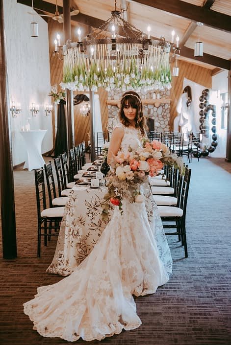 Bride wearing lace gown and holding a crescent shaped bouquet designed with coral charm peonies, blush roses, peach ranunculus, silver plumosa and eucalyptus greenery; standing in front of a black and white decorated rectangle table with a tulips hanging from the chandelier at Canyon Ski Resort Open House 2019.