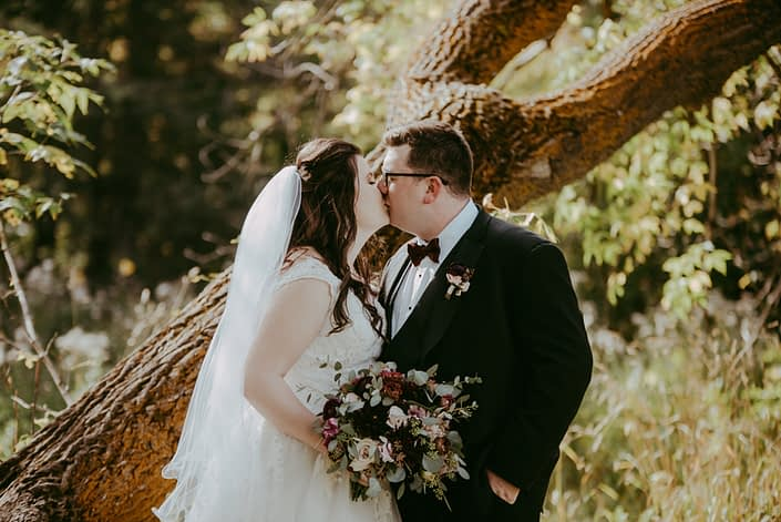 Kaylee and Mitch kissing with burgundy and dusty rose bridal bouquet and boutonniere