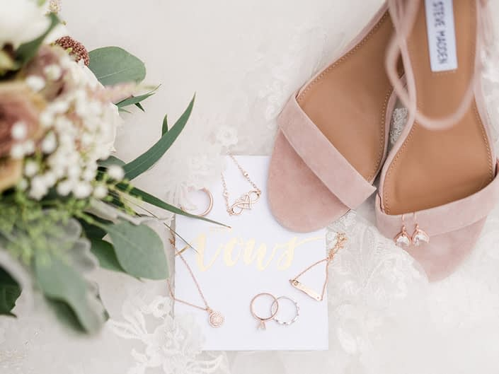 Bride's dusty rose shoes with bouquet, veil, vows and rose gold jewelry flat lay.