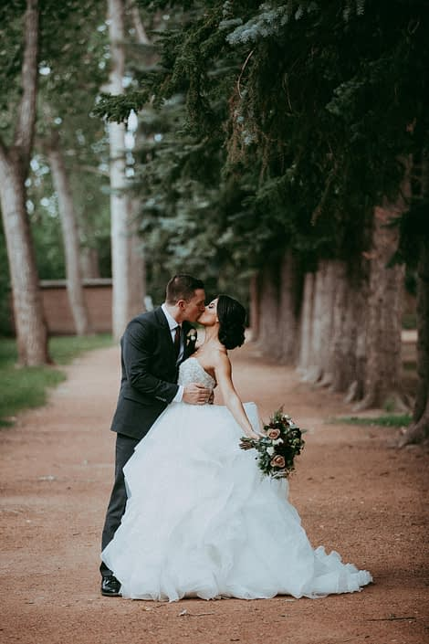 Bride and groom kissing under trees with burgundy and mauve bridal bouquet