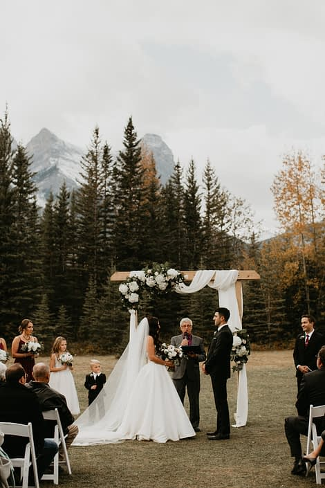 Brittany and Briggs' Elegant Canmore Wedding outdoor ceremony featuring a wooden archway draped with white linens with a corner flower arrangement designed with white hydrangeas.
