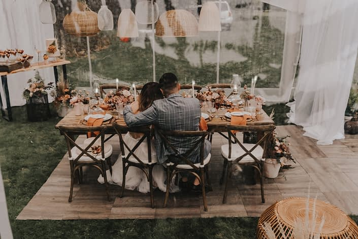 Bride and groom at modern boho styled table with woven baskets, terracotta elements and rust coloured flowers