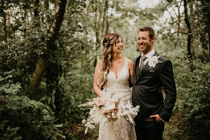 Bride and groom with rustic boho bridal bouquet and boutonniere; bouquet designed with roses, ranunculus, phalenopsis orchids, bleached bracken fern, bunny tail, astilbe, olive branches and eucalyptus