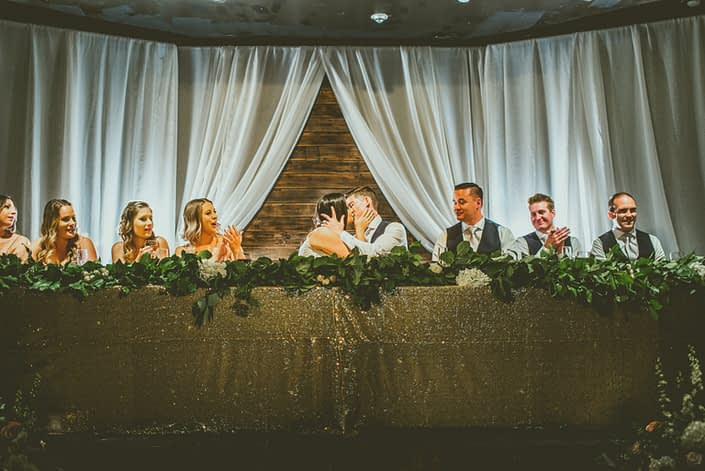 Head table decorated with a gold sparkly tablecloth and a long fresh greenery garland with fairy lights.