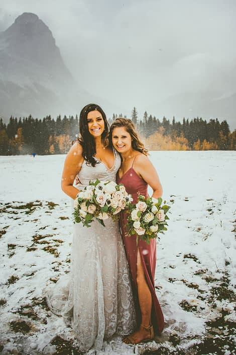 Bride and Bridesmaid standing in the snow carrying bouquets made of blush, white and mauve roses with greenery.