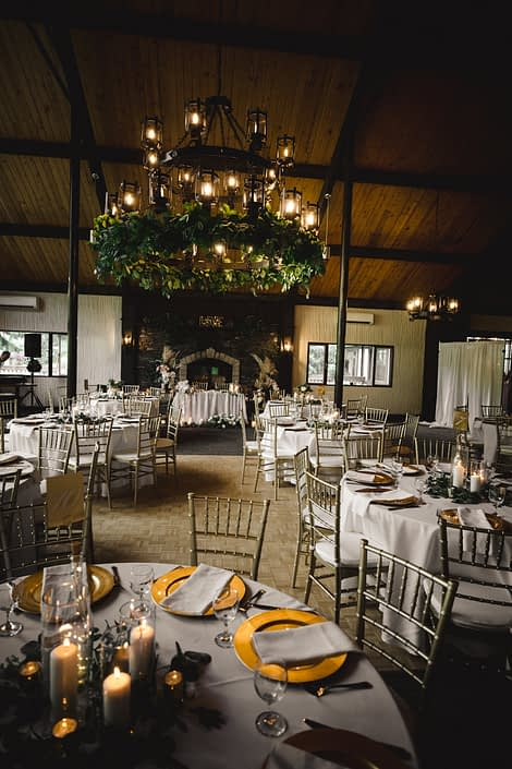 Reception hall at Canyon Ski Resort for Sandra and Brandon's Boho Glam Wedding featuring a greenery garland chandelier arrangement, white linens, and gold accents.