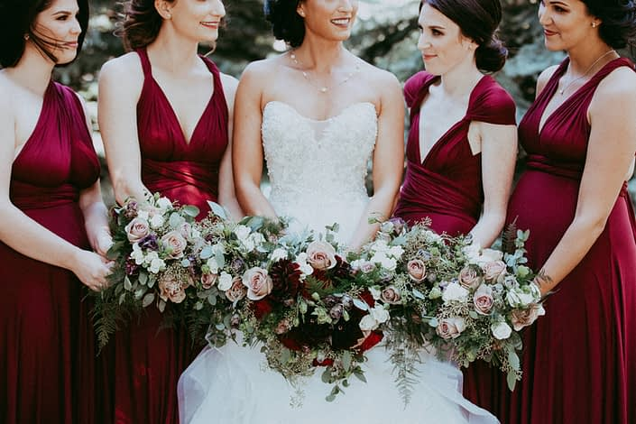 Burgundy and grey wedding bouquets designed with burgundy dahlias, hearts garden roses, black pearl lisianthus, amnesia roses, ivory spray roses, plumosa and eucalyptus
