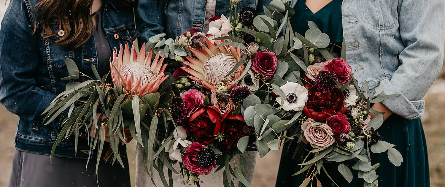Rustic Boho Chic Wedding - bridal bouquet made of king protea, red peonies, pink roses, plum scabiosa, panda anenome, and eucalyptus greenery. Bridesmaid bouquet made of red peony, blush and pink roses, and eucalyptus greenery. Flower girl bouquet made of single king protea and eucalyptus greenery. The bride, bridesmaid and flower girl are all wearing jean jackets.