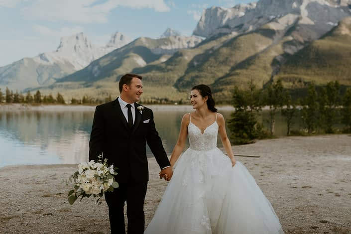 Bride and groom walking by a mountain lake with white bridal bouquet