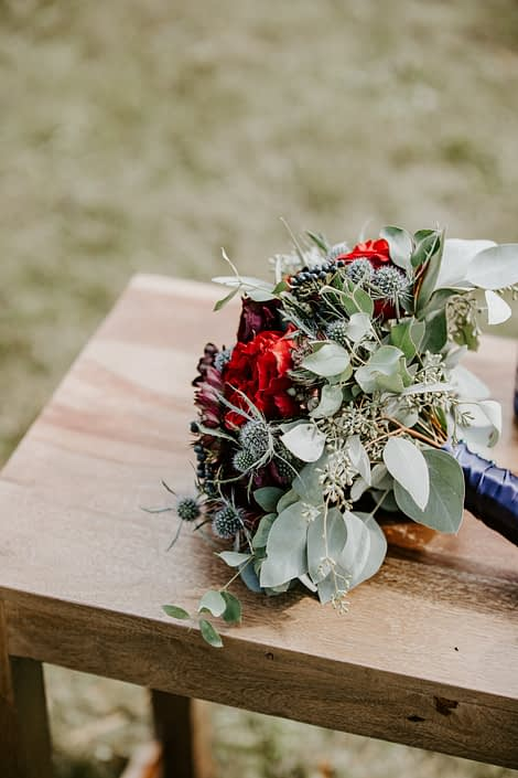 Burgundy and blue bouquet designed with black bacarra roses, ranunculus, astrantia, eryngium and blue viburnum berries wrapped with a blue satin handle