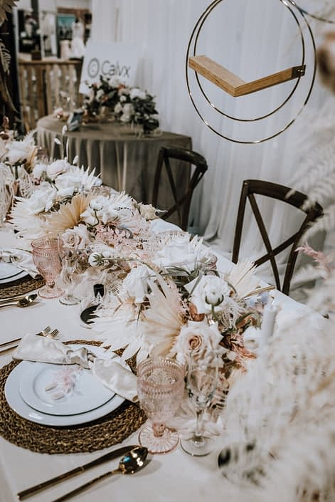 Table-scape at the With This Ring Bridal Gala featuring a long ivory and blush centrepiece with dried and fresh florals and foliage.
