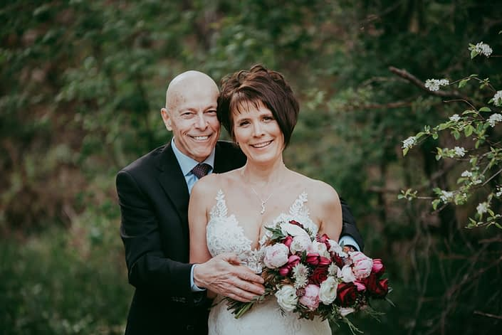 Sandra and David embracing with an elegant pink and burgundy bridal bouquet designed with peonies, ranunculus, black bacarra roses, scabiosa, tulips, Helleborus, Astrantia and, maple leaves, juniper, purple sage and Eucalyptus greenery.