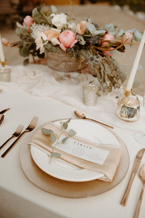 Place setting featuring gold, blush and ivory with a sprig of eucalyptus