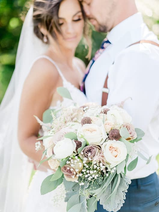 Bride standing with groom holding bouquet made with rose gold painted scabiosa pods, dusty rose quicksand and amnesia roses, blush white o'hara garden roses, white ranunculus, pink astilbe, babies breath, and grey toned greenery such as dusty miller and eucalyptus.