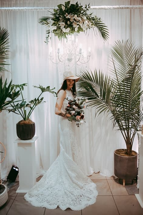 bride with tropical plants in front of white backdrop with chandelier and tropical palm leaf and lily flroal arrangement wearing wedding dress and beige hat and holding a bridal bouquet
