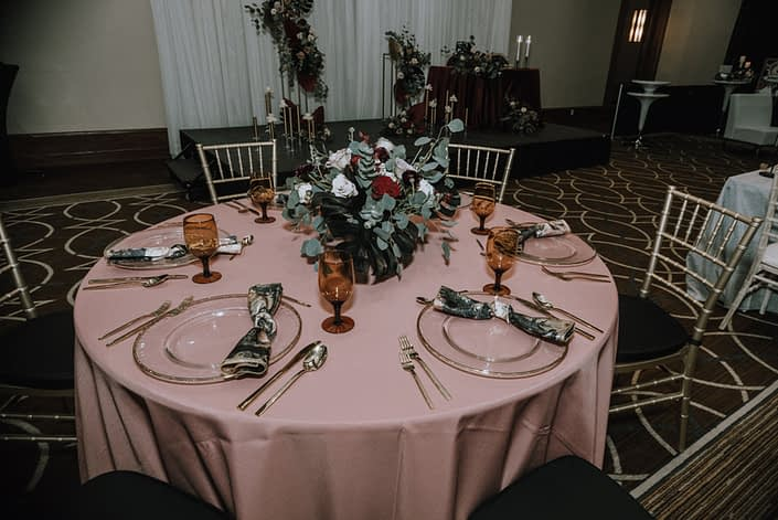 Cambridge Bridal Show 2020 - Round tablescape with blush pink table cloth and low centrepiece made of black dyed monstera leaves, red and blush roses, and eucalyptus greenery.