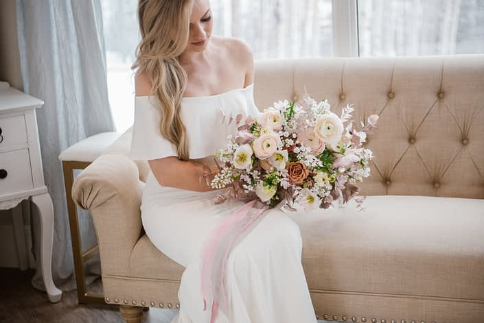 Bride with pink and white bridal bouquet with minimal greenery; designed with ranunculus, hellebores, alyssum, pink bleached italian ruscus, rose gold painted eucalyptus, rose gold painted plumosa