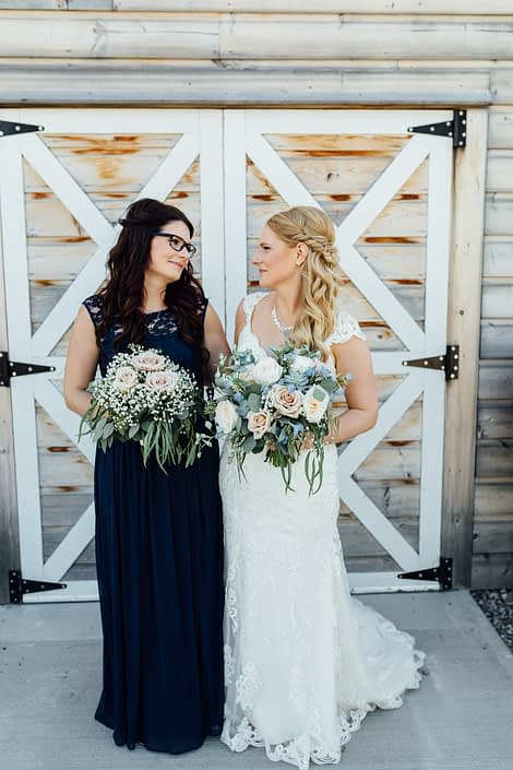 Bride and bridesmaid beside barn doors holding bouquets made of roses and babies breath with eucalyptus greenery; bridal bouquet also features succulents and blue delphiniums.