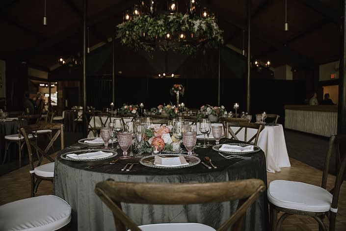 Canyon Ski Resort Open House 2019 tablescape featuring charcoal grey linens, clear and blush table settings, and a blush and coral floral arrangement with silver metallic and greenery accents.
