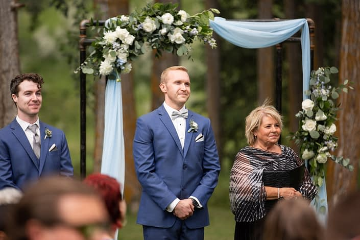 Groom wearing blue suit and boutonniere under archway covered with blue and white flowers such as delphinium, eryngium, ranunculus and roses