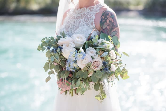 Amy's pink and blue bridal bouquet designed with white o'hara garden roses, quicksand roses, ranunculus, delphinium, astilbe, eryngium, and eucalyptus.