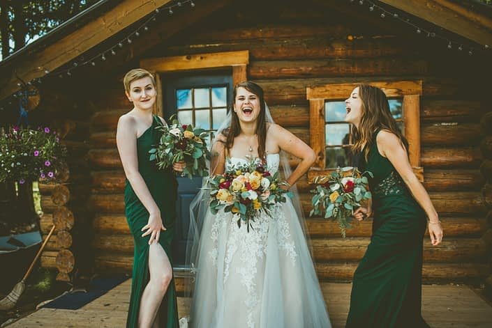 Bride and bridesmaids with mustard yellow bouquets accented by ivory and burgundy.