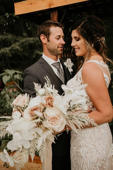 Bride and groom with blush and white rustic boho bridal bouquet featuring roses, ranunculus, orchids, bunny tail, bleached bracken fern and olive branches