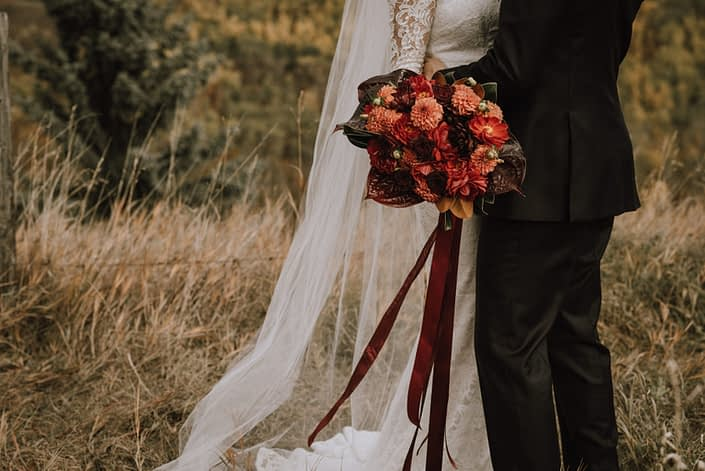 bride and groom in rustic field with lace dress and bouquet with orange dahlia and black bacarra roses and anthuriums and magnolia leaves and trailing ribbons
