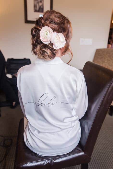 Bride Amy wearing a white bridal robe with blush pink ranunculus hair flowers.
