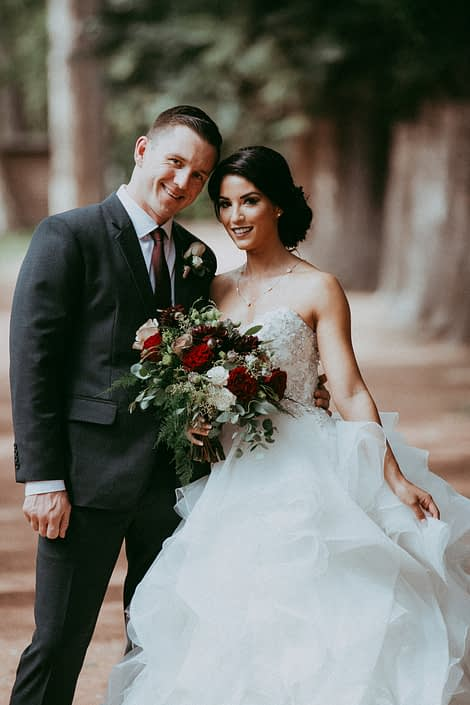 Rikki Lee and Jake, bride and groom, with burgundy and mauve bridal bouquet featuring dahlias, hearts garden roses, amnesia roses, eucalyptus and plumosa