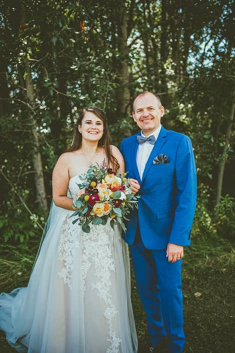 Bride and father of the bride with mustard yellow bridal bouquet with accents of ivory and burgundy flowers.