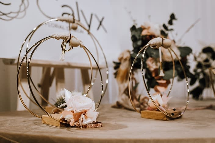 Gold hoop and wood decor with a small blush pink rose corsage on a rose gold bracelet.