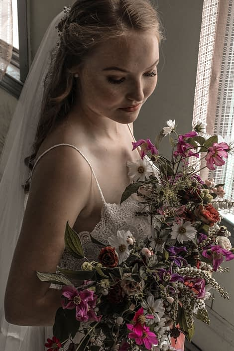 Pink Vintage Photoshoot - model wearing ivory bridal gown and veil holding white, pink and purple wildflower bouquet made of cosmos and greenery.